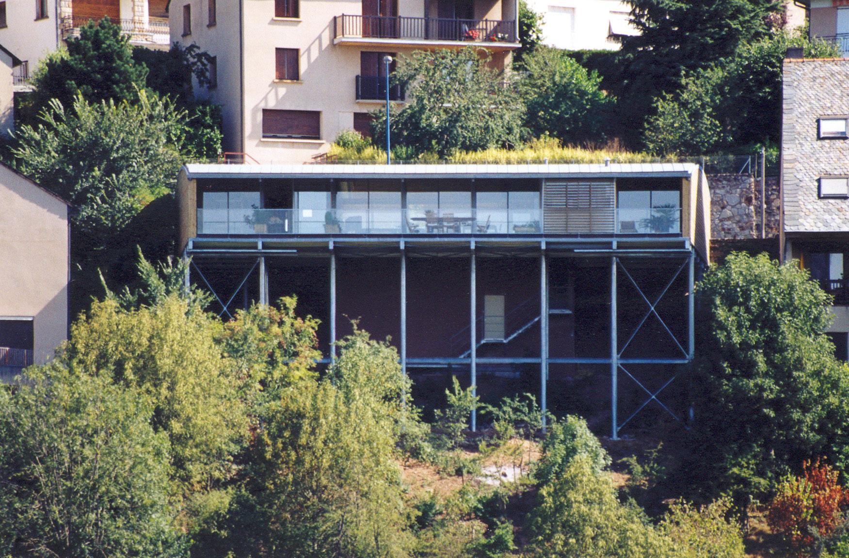 Une maison construite dans la pente sur pilotis for Architecture suspendue