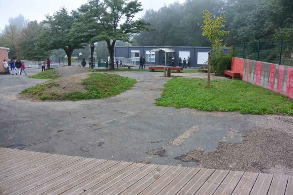 Au pied des robiniers, le centre enherbé de la cour devient une respiration et permet de délimiter différents espaces de jeux.